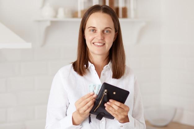 Uśmiechnięta pozytywna kobieta o przyjemnym wyglądzie, ubrana w białą koszulę w stylu casual, stojąca w jasnej kuchni i trzymająca portfel z pieniędzmi, patrząca na kamerę z radosnym wyrazem twarzy.