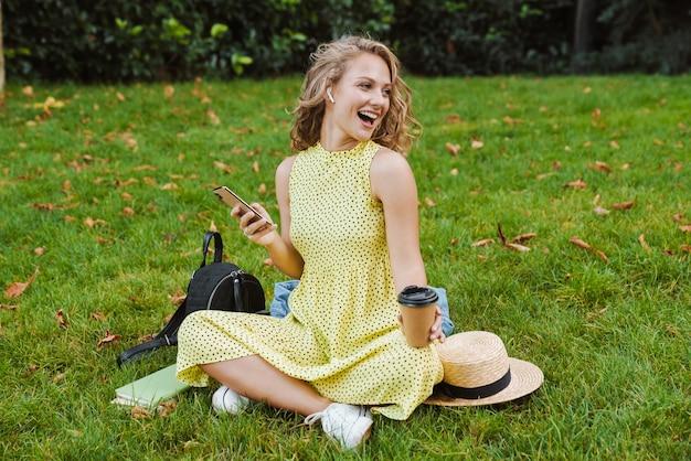 Uśmiechnięta pozytywna kobieta siedzi na trawie na świeżym powietrzu w parku przyrody, trzymając kawę za pomocą telefonu komórkowego, słuchając muzyki przez słuchawki.