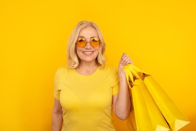 Uśmiechnięta pozytywna kobieta trzyma wiele toreb na zakupy w okularach przeciwsłonecznych.