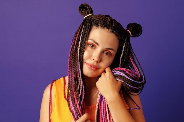 Uśmiechnięta pozytywna młoda kobieta z kolorowymi afrykańskimi warkoczami