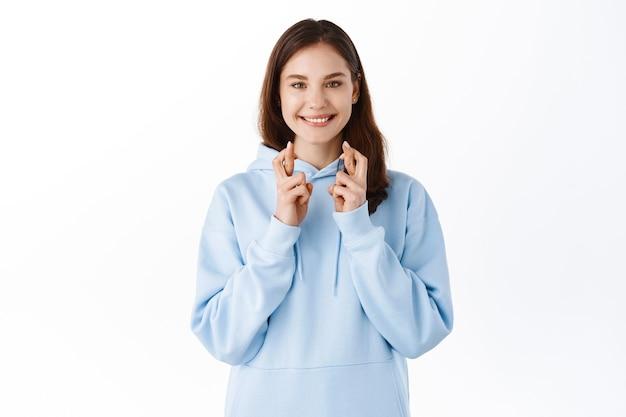 Uśmiechnięta pozytywna studentka życząca, oczekująca dobrych wieści, wygląda z nadzieją i trzyma kciuki na szczęście, modląc się o spełnienie marzeń, biała ściana