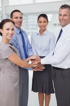 Uśmiechnięta praca zespół łączy ręce razem