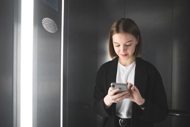 Uśmiechnięta pracownica biurowa w windzie za pomocą smartfona.