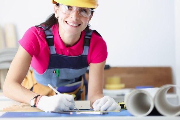 Uśmiechnięta pracownica budowlana w żółtym kasku pochyliła się nad planami