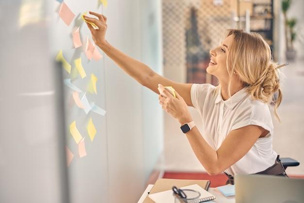 Uśmiechnięta pracownica korzystająca z samoprzylepnych papierowych notatek podczas pracy w nowoczesnym biurze