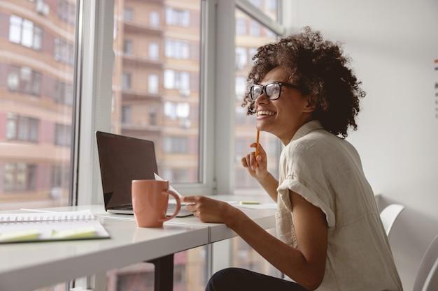 Uśmiechnięta pracownica siedząca przy oknie i pracująca
