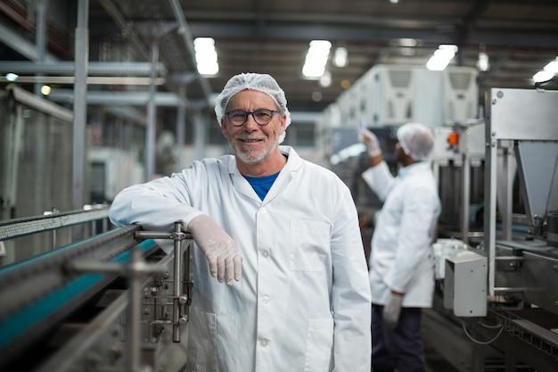 Uśmiechnięta pracownik fabryczny pozycja obok linii produkcyjnej