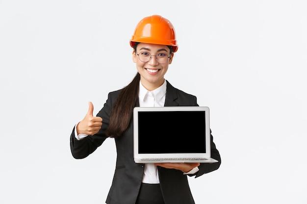 Uśmiechnięta profesjonalna architektka, kierownik budowy w fabryce pokazująca wykres, pozytywny diagram, unosząca kciuk w górę w aprobacie i trzymająca ekran z widokiem na laptopa, noś kask ochronny