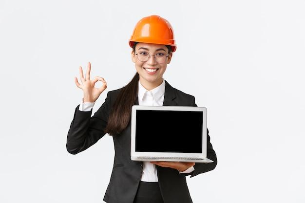 Uśmiechnięta profesjonalna architektka, kierownik budowy w fabryce pokazująca wykres, pozytywny diagram, zrób dobry gest w zatwierdzeniu i trzymając ekran z widokiem na laptopa, noś kask ochronny
