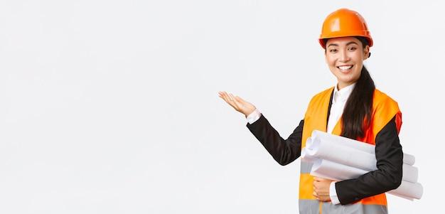 Uśmiechnięta profesjonalna azjatycka architektka, inżynier w kasku ochronnym przedstawia projekt budowlany, wskazując ręką w lewo jako plan noszenia, przemawiając, wprowadzając wykres lub plan budowy