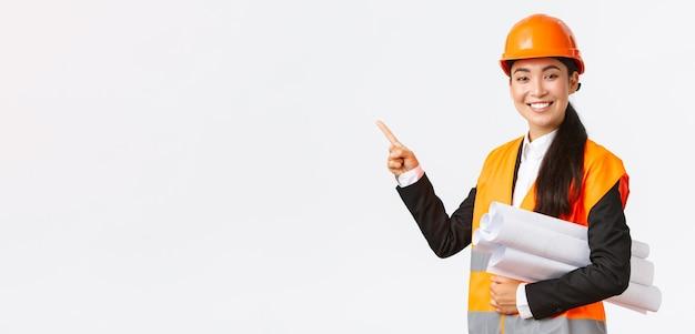 Uśmiechnięta profesjonalna azjatycka inżynierka architekt w kasku przedstawia projekt budowlany ...