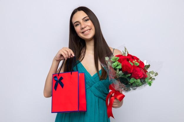 Uśmiechnięta przechylająca się głowa piękna młoda dziewczyna na szczęśliwy dzień kobiety trzyma bukiet z torbą na prezenty na białym tle