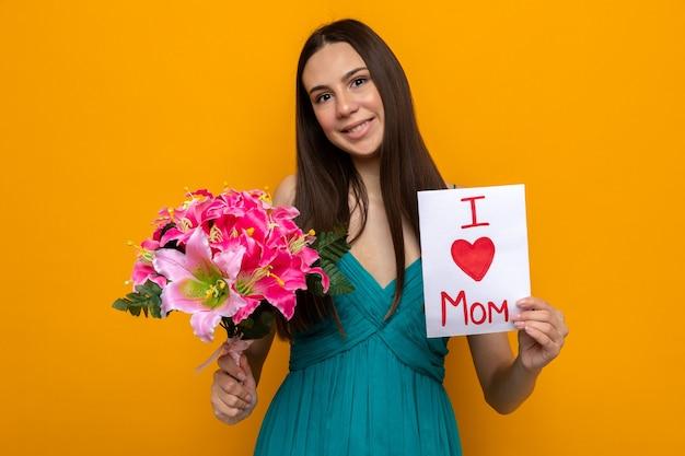 Uśmiechnięta przechylana głowa piękna młoda dziewczyna z bukietem i kartką z życzeniami na dzień matki