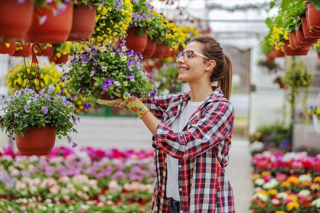 Uśmiechnięta przedsiębiorczyni kobieta stojąca w szklarni i dbająca o kwiaty.