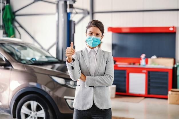Uśmiechnięta, przyjazna kobieta sprzedająca samochód z maską stojącą w garażu salonu samochodowego i pokazująca kciuki do góry