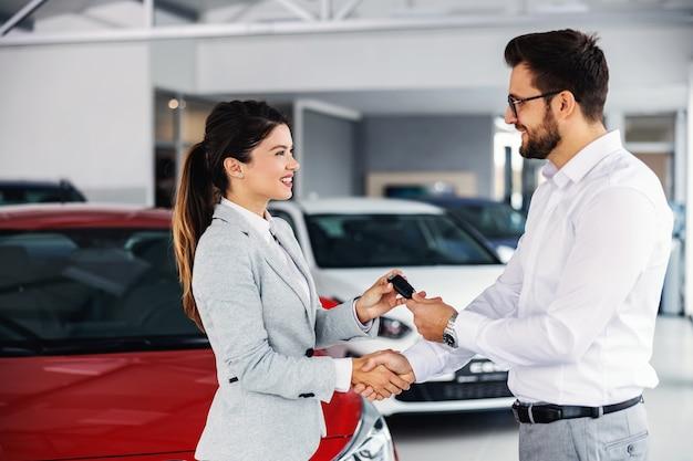 Uśmiechnięta, przyjazna kobieta sprzedawca samochodów stoi w salonie samochodowym z klientem i wręcza mu kluczyki do samochodu.