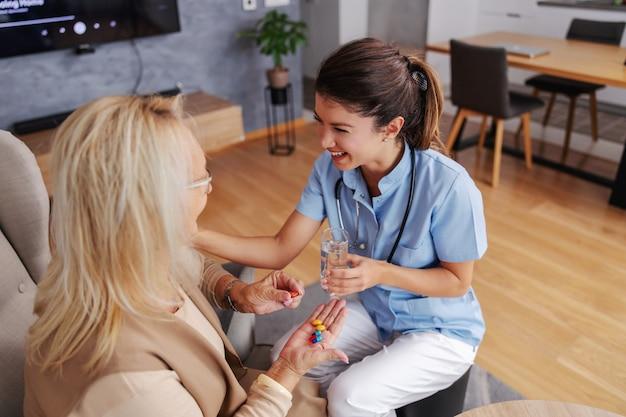 Uśmiechnięta przyjazna pielęgniarka siedzi w domu ze starszą kobietą, podając jej szklankę wody. kobieta siedzi i trzyma pigułki i witaminy.