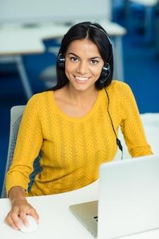 Uśmiechnięta przypadkowa bizneswoman w swetrze siedzi w swoim miejscu pracy ze słuchawkami w biurze