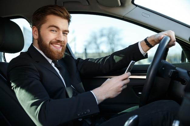 Uśmiechnięta przystojna biznesowa kobieta używa telefon podczas gdy siedzący w samochodzie