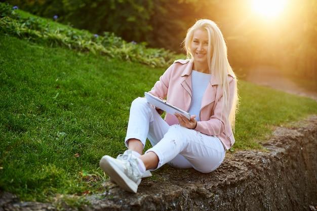 Uśmiechnięta przystojna kobieta słucha relaksującą muzykę w hełmofonach z jej telefonem komórkowym lub pastylką przy parkiem. student słucha wykładu online i przygotowuje się do egzaminów.