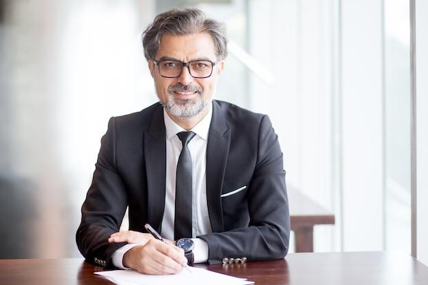Uśmiechnięta przystojny biznes lider dokonywanie notatek