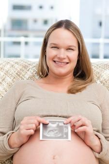 Uśmiechnięta przyszłościowa mama pokazuje echography kamera