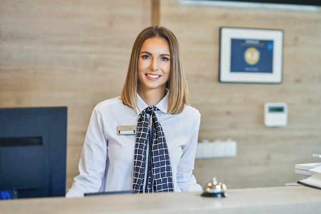 Uśmiechnięta recepcjonistka w recepcji hotelu front