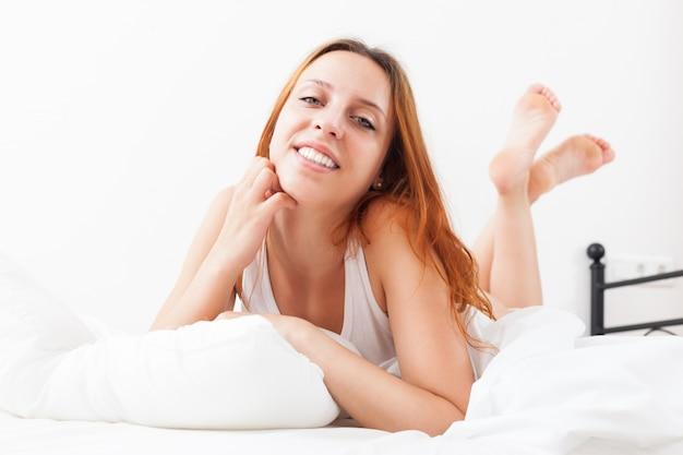 Uśmiechnięta red-haired piękna kobieta budzi się w swoim łóżku w domu