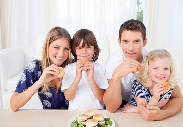Uśmiechnięta rodzina jedzenie hamburgerów w salonie