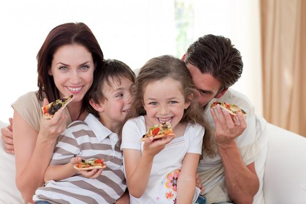 Uśmiechnięta rodzina jedzenie pizzy