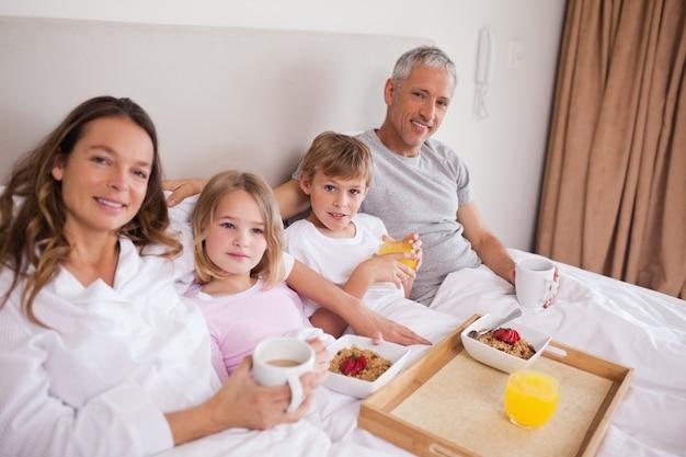 Uśmiechnięta rodzina ma śniadanie w sypialni
