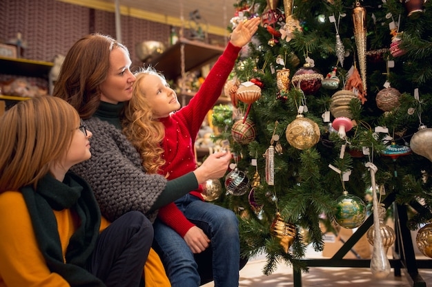 Uśmiechnięta rodzina, matka i dzieci szukające dekoracji domu i świątecznych prezentów w sklepie domowym
