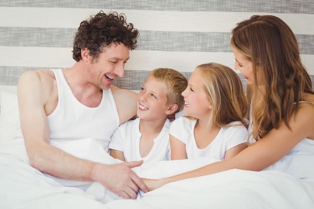 Uśmiechnięta rodzina odpoczywa na łóżku