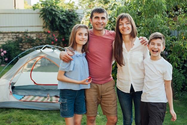 Uśmiechnięta rodzina stoi razem przed namiotem obozu w parku