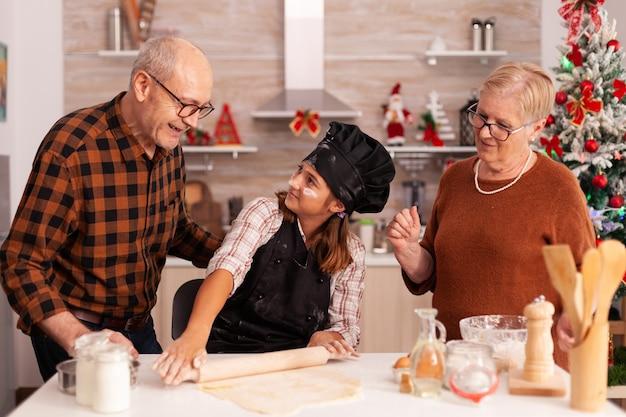 Uśmiechnięta rodzina stojąca przy stole w świątecznej udekorowanej kuchni kulinarnej świętującej święta bożego narodzenia
