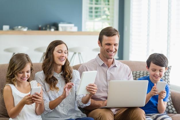 Uśmiechnięta rodzina używa cyfrową pastylkę, telefon i laptop w żywym pokoju