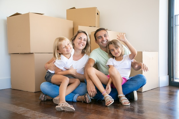 Uśmiechnięta rodzina z dziećmi siedzi na podłodze w pobliżu pudeł kartonowych i relaks
