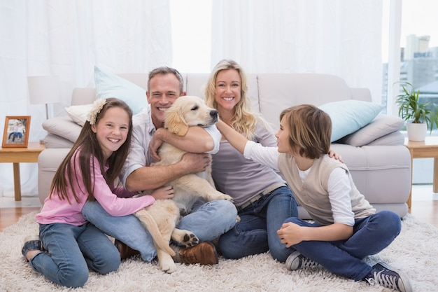 Uśmiechnięta rodzina z ich zwierzę domowe żółtym labradorem na dywaniku