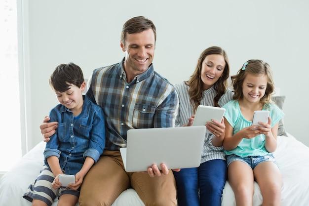 Uśmiechnięta rodzina za pomocą laptopa, cyfrowego tabletu i telefonu komórkowego w sypialni