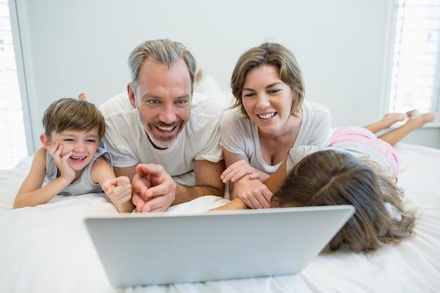 Uśmiechnięta rodzina za pomocą laptopa na łóżku w sypialni