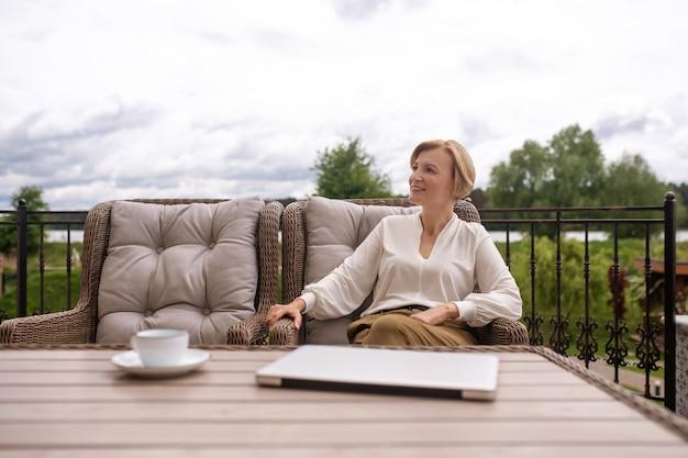 Uśmiechnięta, rozmarzona piękna, wykwintna kobieta siedząca w fotelu przy stole w malowniczej miejscowości odwracającej wzrok