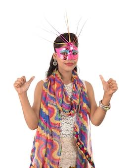 Uśmiechnięta rozochocona dziewczyna jest ubranym karnawał maskę i pokazuje znaka odizolowywającego na biel przestrzeni