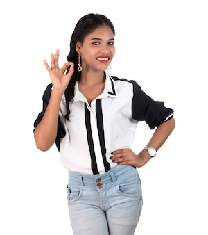 Uśmiechnięta rozochocona dziewczyna pokazuje ok znaka lub aprobaty odizolowywających na biel przestrzeni