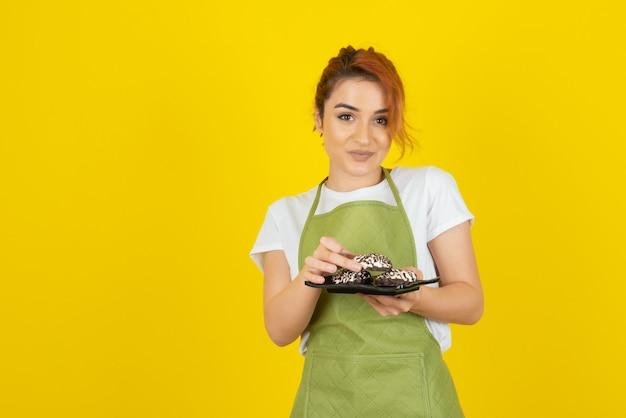Uśmiechnięta ruda bierze świeże ciastko ze stosu na żółtej ścianie