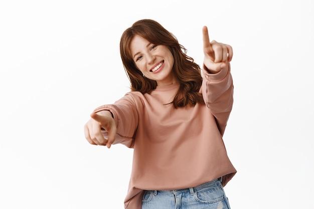 Uśmiechnięta ruda dziewczyna wskazująca palcami, chwaląca cię, wybierająca lub rekrutująca, zapraszająca do przyłączenia się do firmy, stojąca w codziennych ubraniach na białym