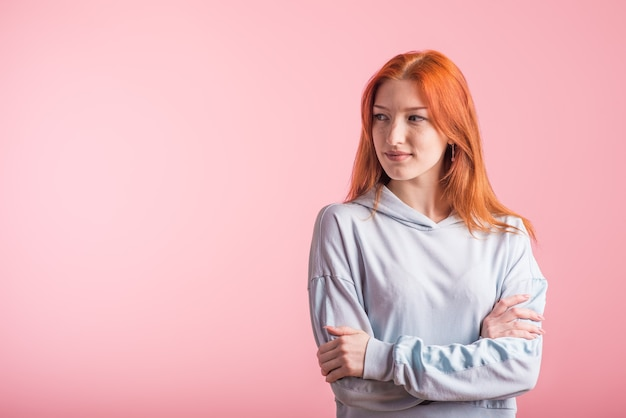 Uśmiechnięta ruda dziewczyna ze skrzyżowanymi rękami w studio na różowym tle