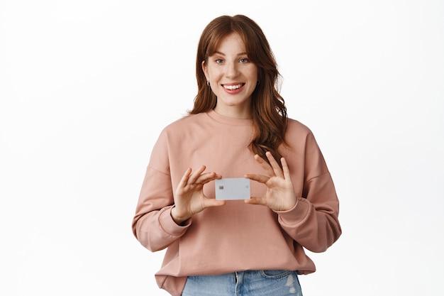 Uśmiechnięta ruda kobieta pokazująca kartę kredytową, polecająca bank, stojąca w zwykłych ubraniach na białym tle