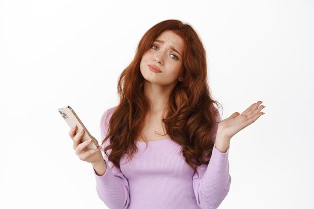 Uśmiechnięta ruda kobieta trzymająca smartfon na białym tle