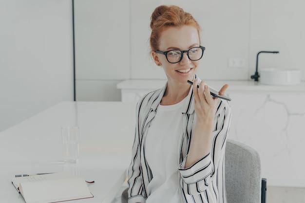 Uśmiechnięta ruda kobieta używa wirtualnego asystenta głosowego nagrywa wiadomość dźwiękową