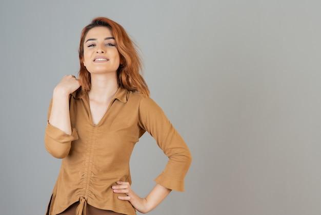 Uśmiechnięta ruda stoi na szarej ścianie